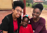 Two MPH students, Elizabeth Stephenson (left) and Jenée Russell, pose with a Ugandan child this summer. The students' experience in a rural health clinic and maternity center reaffirmed their chosen career path. Four other School of Public Health students spanned the globe, spending time in Ireland, China and Haiti.