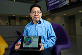 Dr. Dai holding his laptop facing towards the camera with an image of his research on the screen