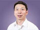 Portrait of Dr. Fangqun Yu with and open-collared white dress shirt with a purple background. Dr. you appears calm, comfortable with a relaxed and happy facial expression.