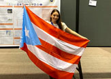 Kayleen Torres Maldonado displays the Puerto Rican flag in front of her research at the American Meteorological Society Annual Meeting in Boston, January 2020.