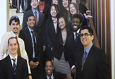 Smiling MBA students standing on staircase