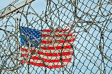 Flag waving on a pole behind prison fences