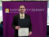 Prof Rich Schneible holding award certificate