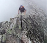 man climbing on mountain in foggy environment