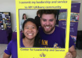 UAlbany students pose behind a coloful Student Affairs clad cardboard frame