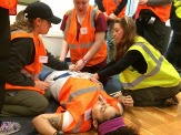Students kneeling on the ground delivering first aid to a disaster victim in a simulated response exercise