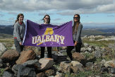 From left: UAlbany students Celia Werner '21, Chelsea Elizabeth Snide '19, and Allison Finch '20 hold up the UAlbany flag as they stand on a mound of rocks in Greenland.