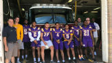 Members of the UAlbany football team standing in front of firetruck with firefighters during their visit to the firehouse to pass out tickets.