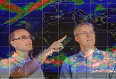 Professors Ryan Torn and Christopher Thorncroft study a weather map
