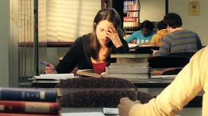 Screenshot from Video, a student studying with her hand on her forehead in frustration.