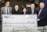 five people stand holding an enormous ceremonial check for $30,000 to the School of Business from the CPA firm UHY