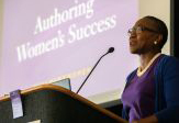 "Winsome Foderingham speaks at a lecturn in front of the projected words ""Authoring Women's Success"""