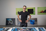 Photo of Danny Goodwin posing in front of paintings at the Boor Sculpture Studio.