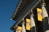 Yellow UAlbany banners hang from the ornate columns of Draper Hall