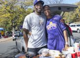 A couple stands in frount of their tailgating picnic.