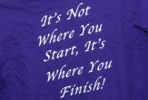 "A purple T-shirt with white letters reading: ""It's not where you start, it's where you finish!"""