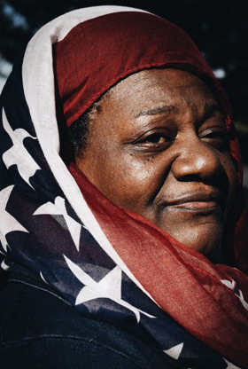 Woman wearing American flag head covering.