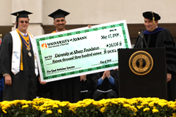 Class of 2008 speaker Nicholas Fahrenkopf presents a check for more than $16,300 to purchase a new ambulance for Five Quad.