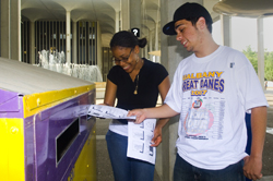 Two UAlbany students use a recycling bin on campus.
