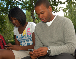 Two students check their cell phones for a text message.