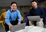 UAlbany atmospheric scientists Aiguo Dai and Fangqun Yu sit with laptops in the University Hall atrium.