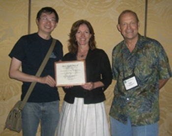 From left, Lei Zheng and Theresa Pardo accept the award from Jochen Scholl.