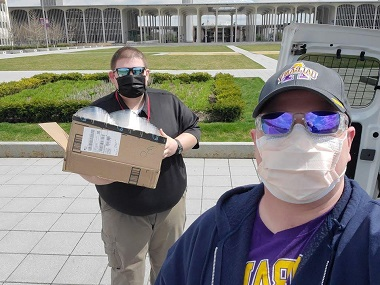 Stephen Conard (right) hands off a box of donated face shields to Eric Gaunay, CEHC alum and emergency preparedness coordinator at the Rensselaer County Bureau of Public Safety.