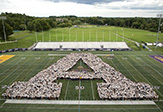 "UAlbany's new students pose in a ""giant A"" for the annual class photo on Bob Ford Field."