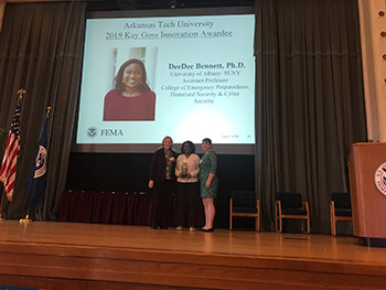 DeeDee Bennett accepts 2019 Kay Goss Technology and Innovation Award on stage at the Federal Emergency Management Agency (FEMA) Higher Ed Symposium.