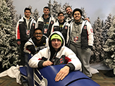 "UAlbany's ""Overwatch"" team takes a photo with a bobsled at the Empire State Winter Games in Lake Placid."