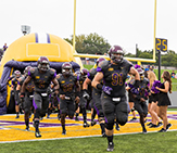 UAlbany Football runs out from inflatable helmet.
