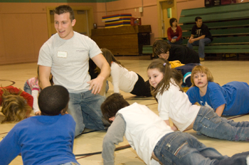 Children do push-ups as Greg Giambone tells them about the benefits of exercise.