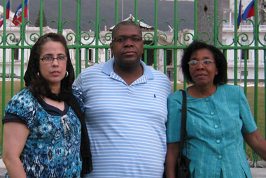 Maritza Martinez, Patrick Romain, and Monette Fils in front of the damaged Presidential Palace in Haiti.