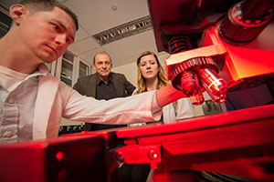 Chemistry Professor Igor Lednev works with recent Ph.D. graduates Claire Muro and Kyle Doty.