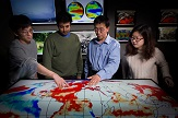 Liming Zhou and students point to a map which displays their research about sea surface temperature variability and its effects on drought in the Congo.
