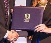 photo of an award and two people shaking hands