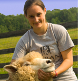 UAlbany student Erin LaBarge holding one of the ewes she studies at Longfield Farm.