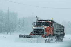 Photo of a plow clearning snow off highway.