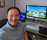 Brian Tang sits in front of computer before virtually speaking with classroom of students.
