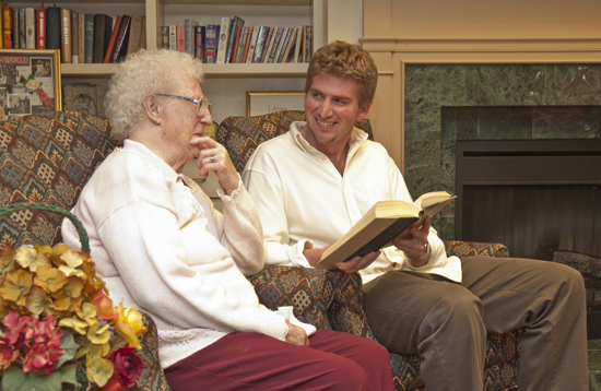 College student reading a book to an older person.