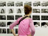 A UAlbany student inspects the photography exhibition of a studio arts major.