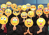 People holding emoji masks.