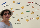 Professor Laurie Feldman in front of a wall of emojis.