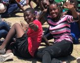 Two Haitian chidren, sitting on the ground, smile and give thumbs-up to the cameraman