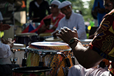 Hands come down upon the conga drum by a player just outside the right frame