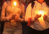 Two girls hold vigil candles over the Parkland shooting