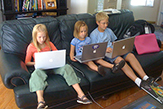 Three children study with laptops while sititing on a home couch