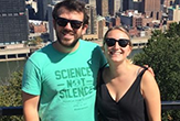 Kyle Bucklin and Elena Brondolo, students who fnished their MBAs while traveling cross country, stand overlooking the Pittsburgh skyline.