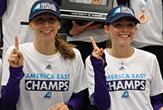 2 victorious America East champion UAlbany women harriers hold up their #1 index fingers.