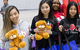 Female students hold up Teddy bears in support of We Care